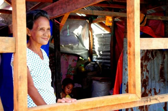 Remedios Petilla, 70, stands proudly in her home which was re-built using a shelter repair kit provided by CARE and our partner ACCORD following Typhoon Haiyan in the Philipines. Image: CARE.