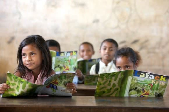 School children in Timor-Leste read their copies of CARE's educational magazine 'Lafaek', which is the only publication in the country that uses the national language Tetun. Image: Jane Dempster/CARE.