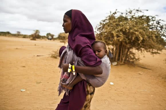 A mother arrives at Dagahaley refugee camp in Kenya with her baby. After registering, CARE provides refugees with items like tarpaulins, kitchen sets, soap, blankets and an initial food supply. Image: Evelyn Hockstein/CARE