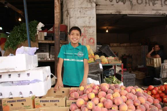 To support his family Aboud works in a vegetable store 12 hours every day.