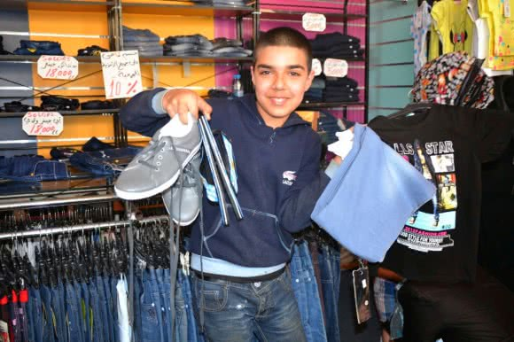 Abu was very happy to buy a new pair of jeans, flip-flops, shirt, socks and sneakers.