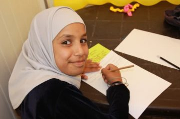 young girl in Syrian refugee camp participating in education program provided by CARE