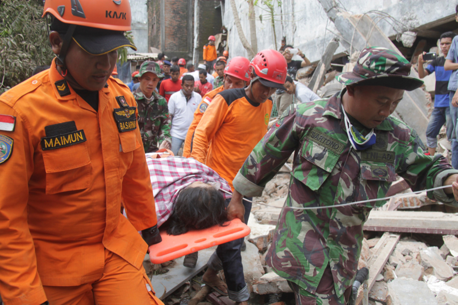 Indonesian rescue workers carry a survivor from a fallen building after an earthquake in the northern province of Aceh, Indonesia. Image: Antara Foto/Ampelsa