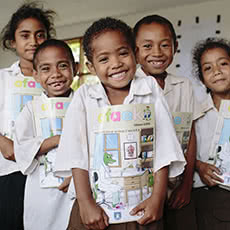 Children pose with a copy of Lafaek. Macalaco primary school, Baucau, Timor Leste.