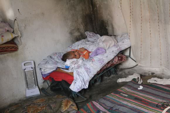 Baby Camar, aged just a month and a half, came to Turkey from Syria aged just days old. His family of eight share this room. ©Kathryn Richards/CARE