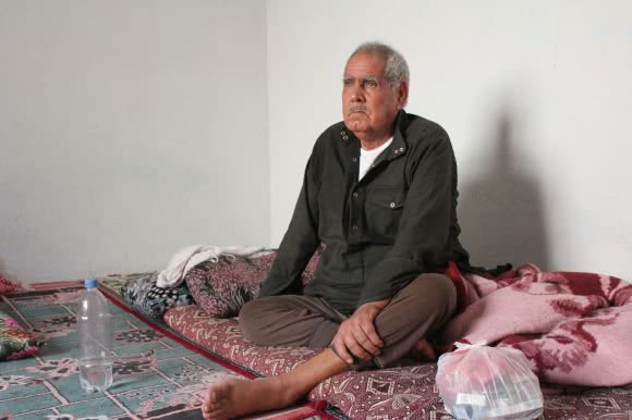 Seventy-year-old Ismail Yousef Hessi came from Kobane when the town came under bombardment. After spending a night on the border, he sits next to a bag of his much-needed medicine. He has just a few days of medicine left. ©Kathryn Richards/CARE