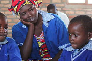 Teacher with students in Rwandan classroom.
