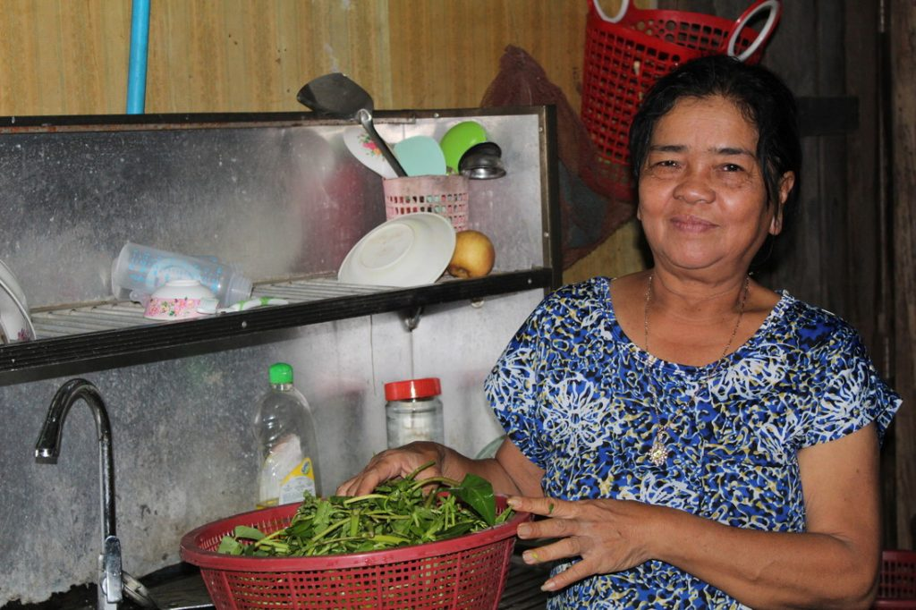 Lady standing proudly in kitchen, washing fresh produce