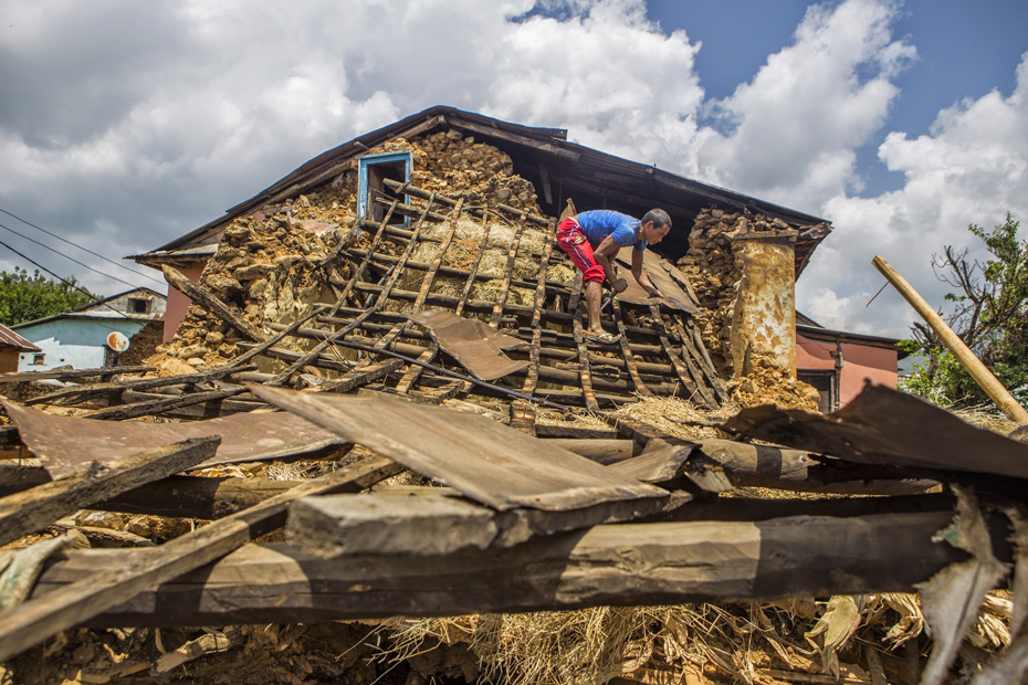 Nepali man rebuilds house after the 25 April earthquake.