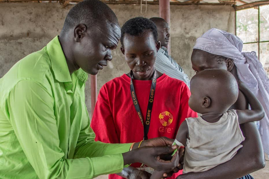 A South Sudanese baby's arm circumference is measured to monitor health and nutrition.