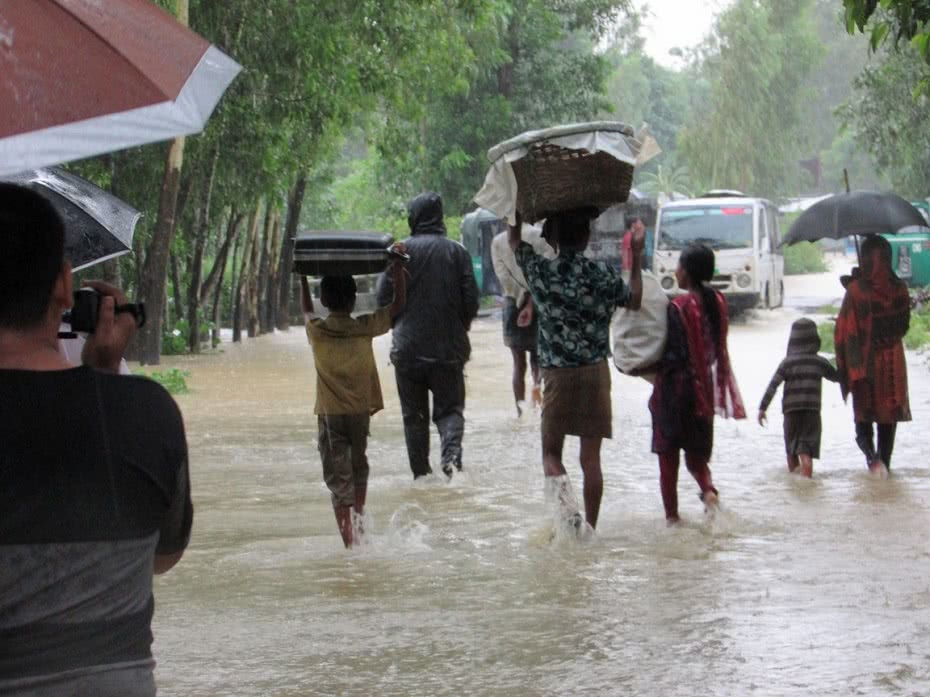 People wade to safety after severe flash floods hit south-east Bangladesh.