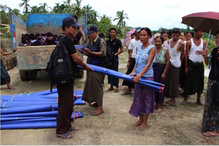 Communities affected by the Myanmar floods receive tarpaulins.
