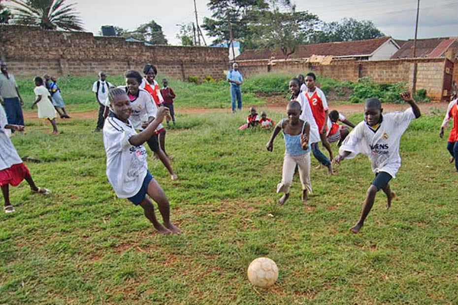 Girls and boys play soccer in Tanzania.