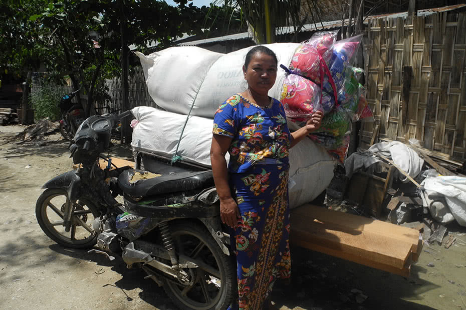 A woman standing next to a vehicle loaded with fabric scraps in Myanmar.