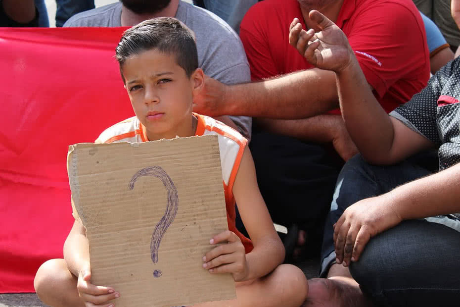 A Syrian boy and refugee holds up a homemade sign with a question mark.