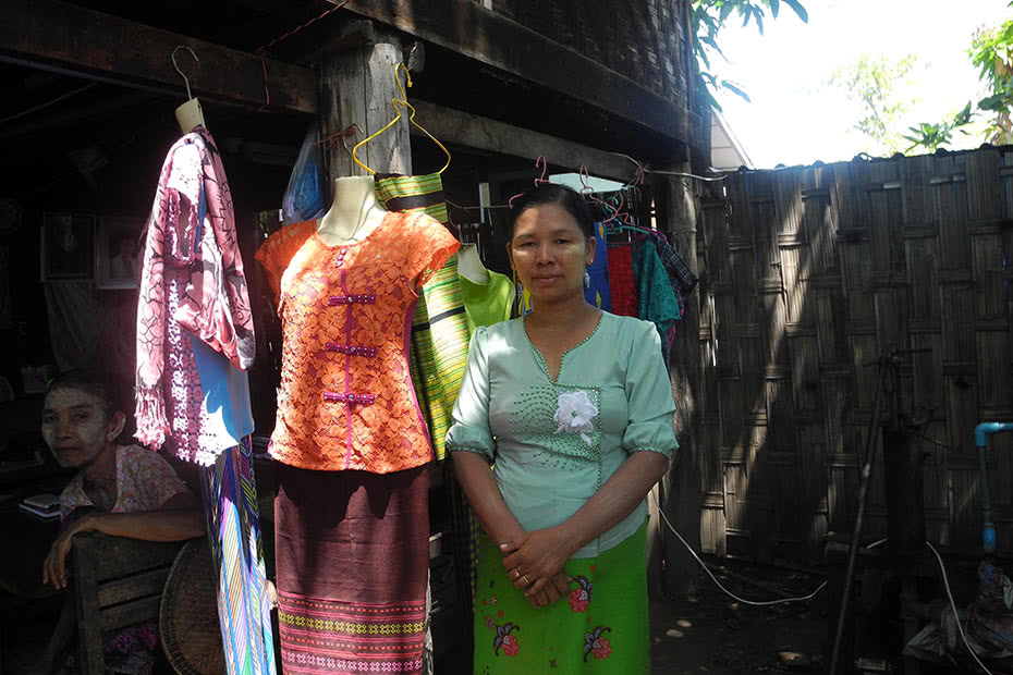 Daw Khin Wyne, a dressmaker, stands outside her shop in Myanmar.