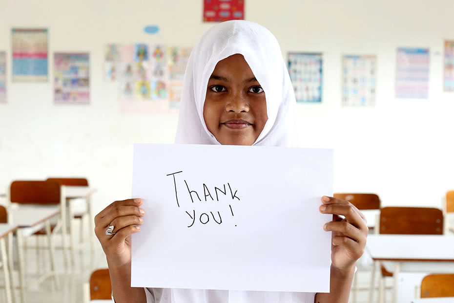 "An Indonesian girl holds up a ""Thank you"" sign 10 years after her family were assisted by CARE during the 2004 Boxing Day tsunami."