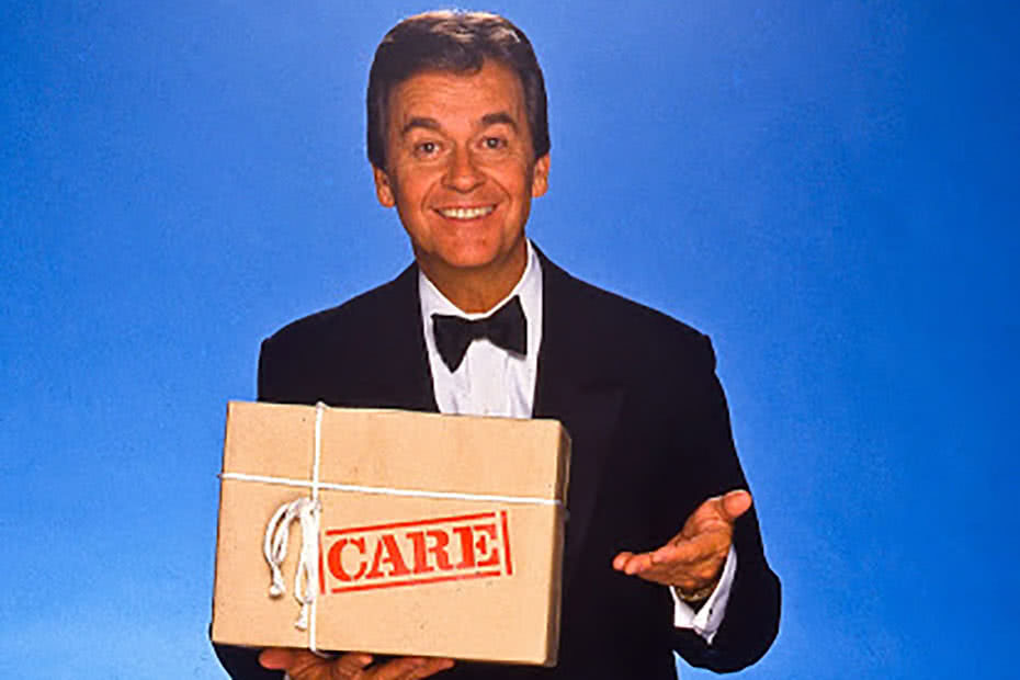 Historical image of American television personality Dick Clarke with a CARE package.