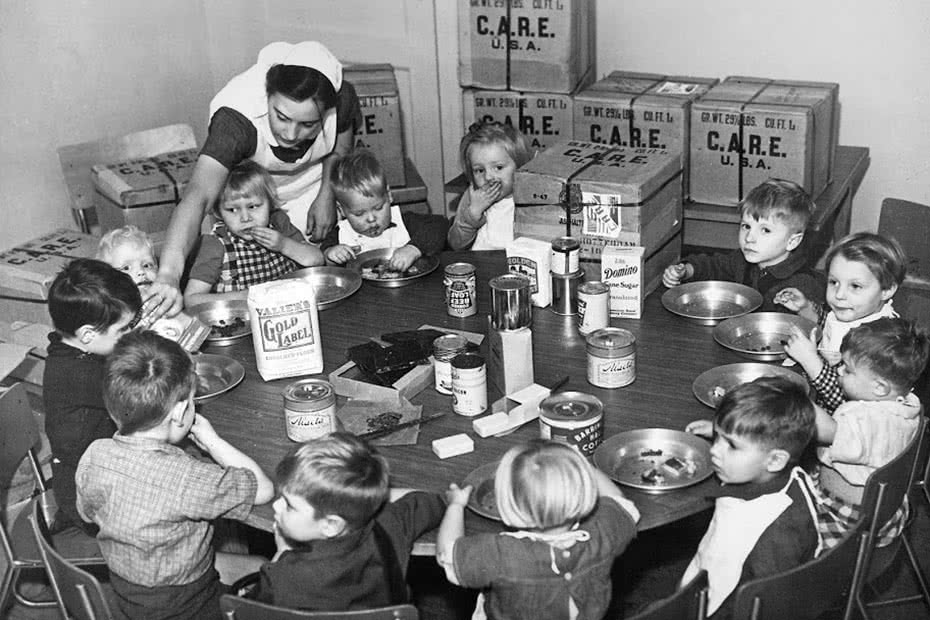 A historical photo of Dutch orphans being fed with CARE packages.