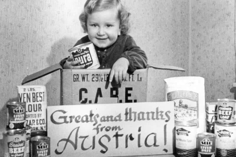 "An Austrian girl poses with a ""Thank You"" sign after her family received a CARE package."