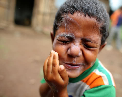 A boy washes his face with soap.