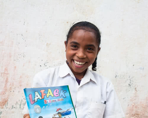 A girl smiles happily holding her schoolbook.