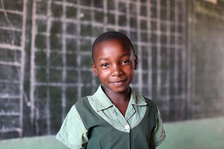 A schoolgirl stands in front of a blackboard in a classroom smiling in Zimbabwe.