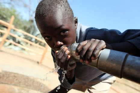 A Zimbabwean child drinks clean water out of a new tap build with the help of CARE.