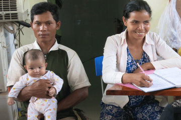 A mother studies while her husband holds their baby.