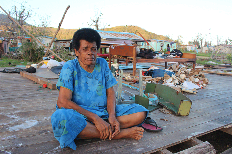Grandmother Eva sits in what's left of her house in her village in the Yasawa Islands.