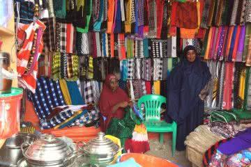 Damac, 40 (left) and Habibo, 35 (right), started their clothing shop after joining a VSLA is Somalia. Photo © Wanjiru Wambugu/CARE