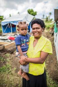 "Following Tropical Cyclone Winston, CARE sent aid through our partners in Fiji, Live and Learn to some of the hardest hit communities. On the mainland, those villages were in the Rakiraki region, where this interview took place. The aid consisted primarily of seedlings and hygiene kits (the red buckets) containing soap bars, toothbrushes, toothpaste, women's hygiene items, and water purification tablets. Alumita's story in her own words: I've got three kids, all girls. The eldest is in school nearby. The next one is in primary school. Before Winston we were here and our source of income was selling cassava root crops and vegetables, and weaving mats. The wind has really affected us. Me, as a mother to three children. At the time my youngest was just a new-born. We least expected Tropical Cyclone Winston to arrive on Saturday. My husband went to the shop. On his way back the wind followed him. We are sitting on the foundation of our house. There is nothing left of the house. When my husband walked in the wind was so strong that we couldn't close the door. As a mother I was very scared. We grabbed what we could and moved to a coroner. The roof started coming off. I told my husband to take the baby to a safer house. I have never seen such winds. I never allowed the fear to take over me so I could be a strong mother to my children. The whole roof was gone and the rain was falling upon us. The experience was very frightening. One of the branches from the mango tree fell into the house. But there was only one corner left to shelter behind. We could feel the floor moving so I grabbed my children and hid them under the floor. They were crying ""Mum please come down here with us – we don't want you to die."" That corner and the floor protected us until the wind went away. CARE and Live and Learn have immensely helped us. In our time of need we – as you can see – the aid you provided us is starting to bear fruits. The seedlings of tomatoes, eggplant"