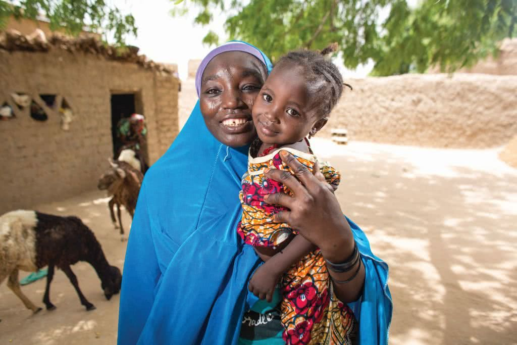"""Haoua from Kagadama village outside Maradi City in Niger, poses for a picture with her daughter outside her home. Haoua is the daughter of Fatchima Aboubacar, a member of the first Village Savings and Loan Association (VSLA), also known as """"Mata Masu Dubara"""" (MMD), which began in 1991. She was married early (Niger has the highest percentage of child brides in the world) and was unable to go to school. She says VSLA (MMD), however, has taught her the value of education, and though one of her own children was married at 15 and is not in school, her other five children are getting the education that she knows will bring them more opportunities than she had. """"My kids will be stronger than my generation, and their kids stronger than theirs,"""" she says."""