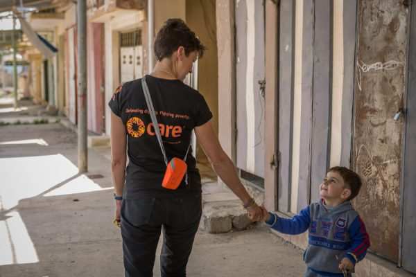Jacqui Symonds, CARE's Head of Programs in Kurdistan Region of Iraq, greets a little boy who has recently returned to his home on the outskirts of Mosul in Iraq. Image © Emily Kinskey/CARE