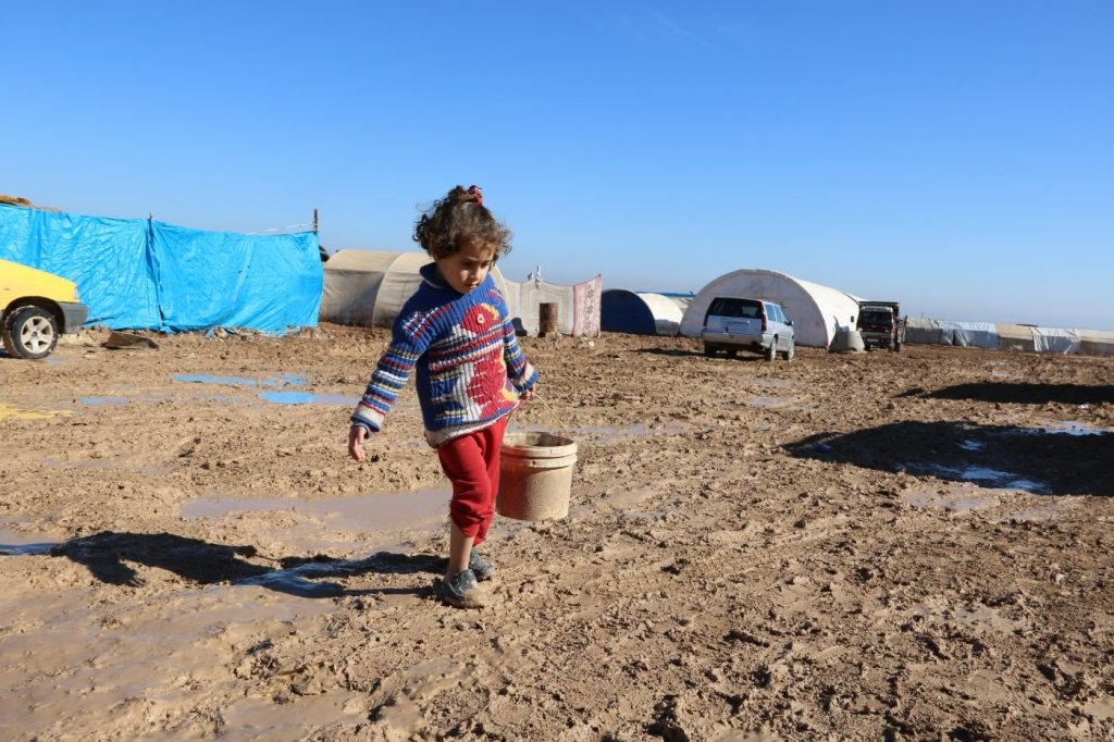 a young girl carrying a bucket through a refugee camp