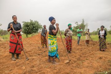 Female farmers in field preparing the ground to plant soy seeds